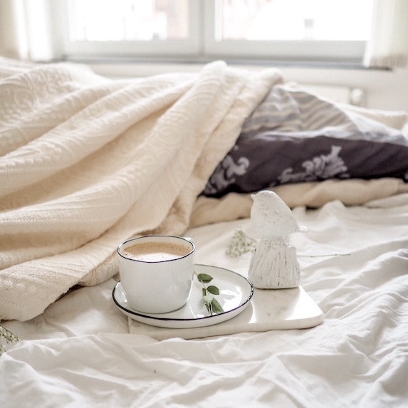 white bed with beige and grey blankets and a cup of coffee on top