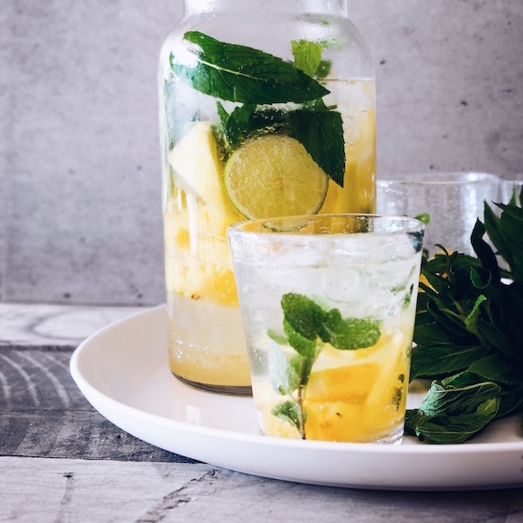 pitcher and glass filled with water, lemon and mint