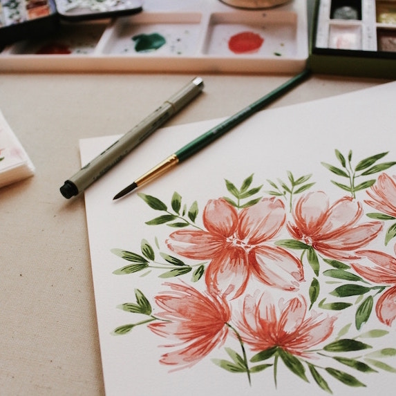 paints, paintbrush and painting of flowers on desk