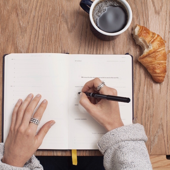 woman writing in journal with coffee and croissant on table