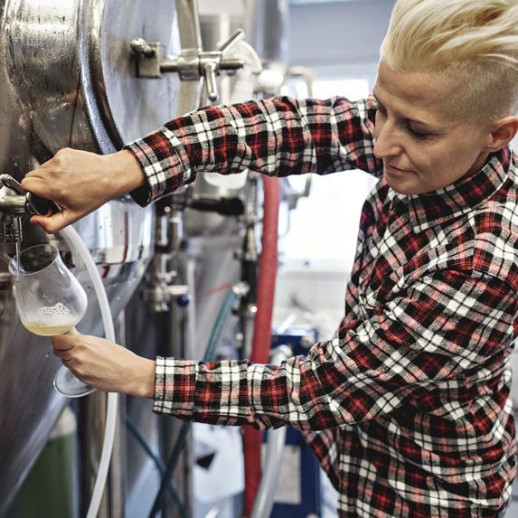 A brewer checking beer