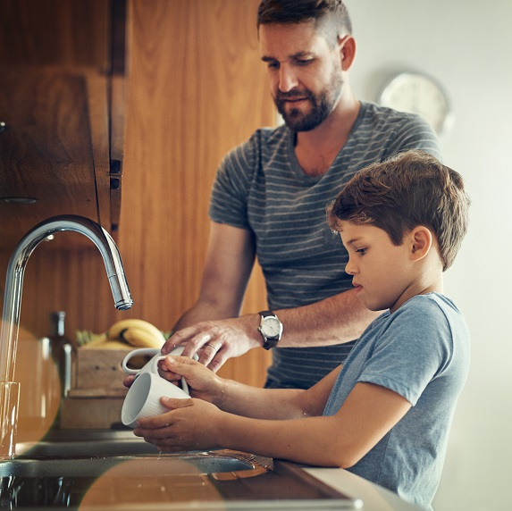 Parent and child washing dishes