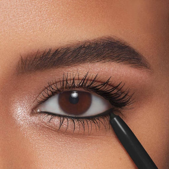 Closeup on a model's eye and the Thrive Causemetics eyeliner she is applying