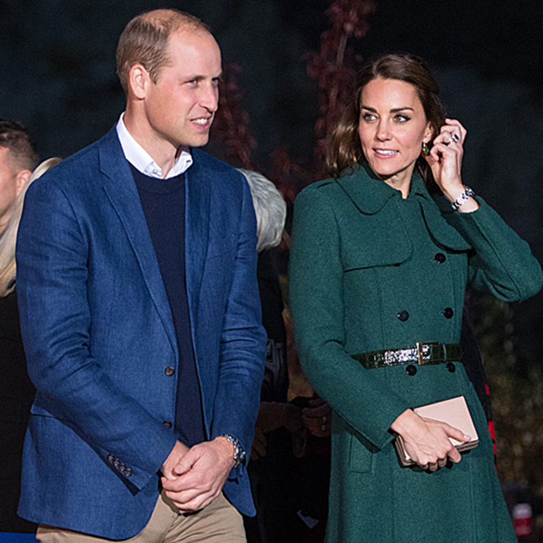 Kate Middleton walking alongside Prince William in a forest green coat