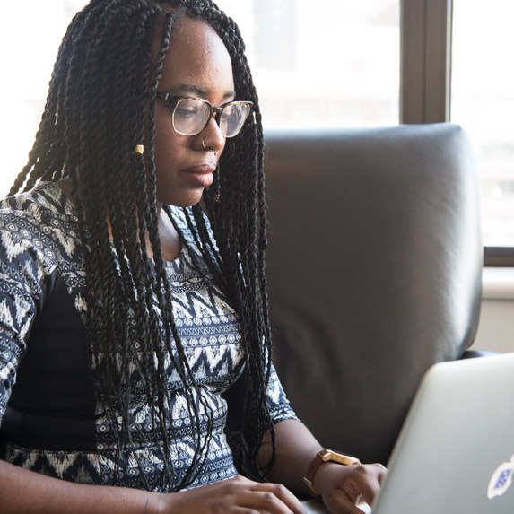 Woman with long hair typing on laptop computer