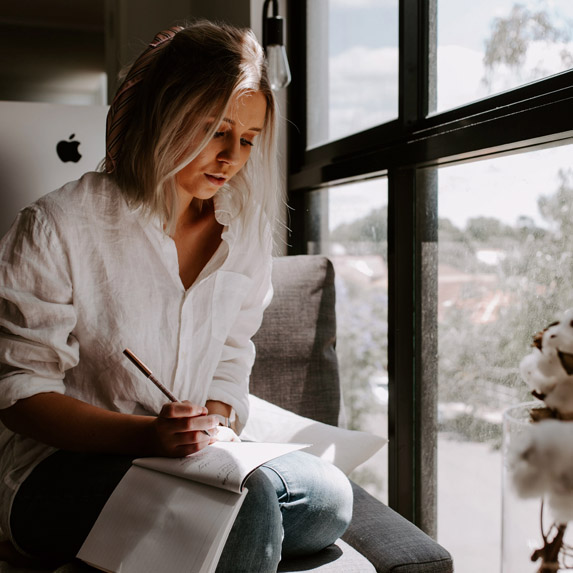 woman sitting while writing on notepad