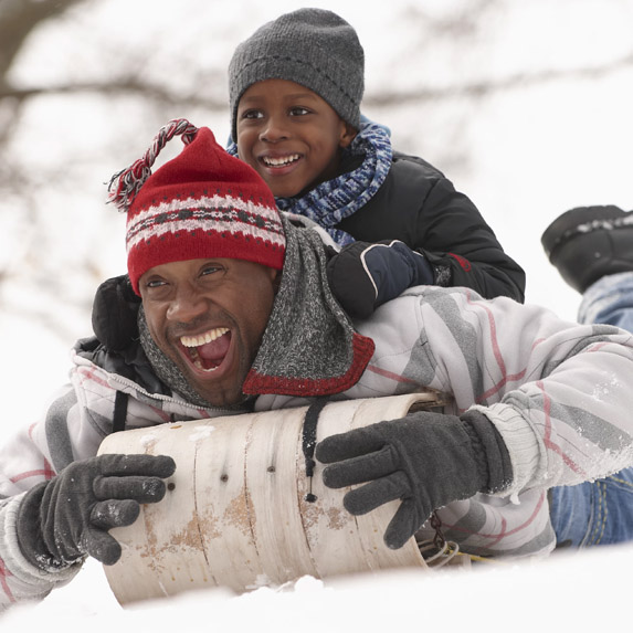 Parent and child sliding down hill on tobbogan