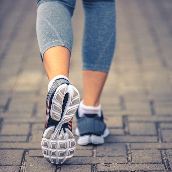 A woman's feet in sneakers preparing for a morning run
