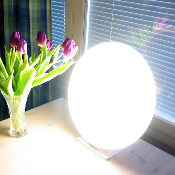 A therapy light shining brightly on a desk next to a vase of flowers