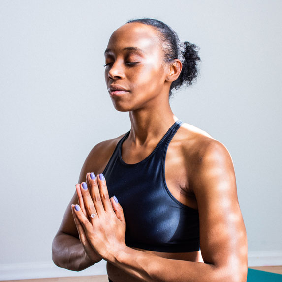 A woman in a meditative pose, dressed in yoga gear