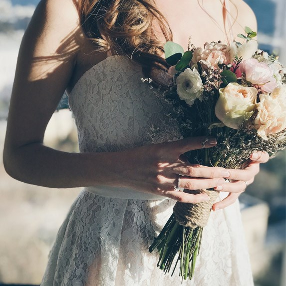 A closeup of a woman's torso in wedding gown, with hands holding the bouquet