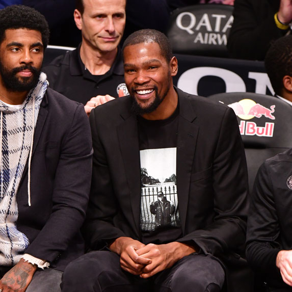 Kevin Durant sits on the sidelines supporting his Brooklyn Nets team while injured.