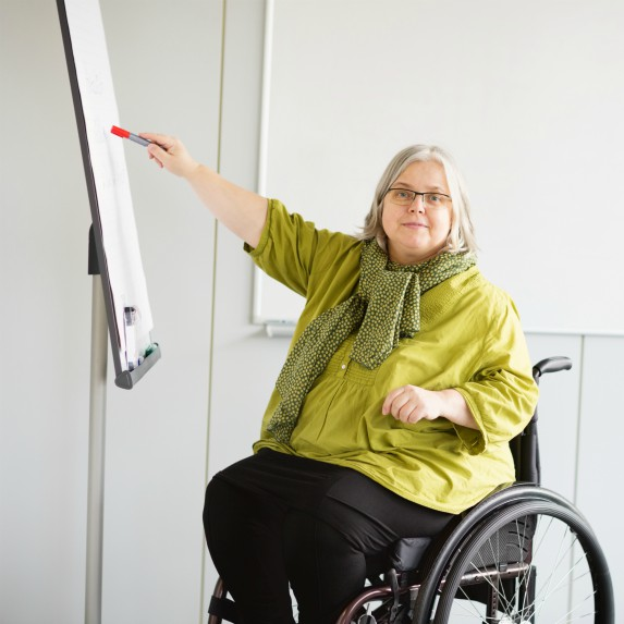 woman in wheelchair writing on paper