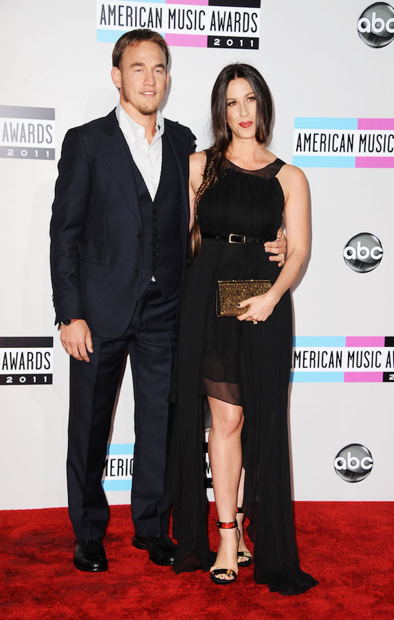 Alanis Morissette wears a black belted dress with a high-slit and strappy sandals as she walks the red carpet of the American Music Awards in 2011 with husband Mario Treadway.