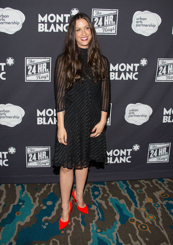Alanis Morissette wears a black dress with sheer details and bright red pumps while attending an event in 2014