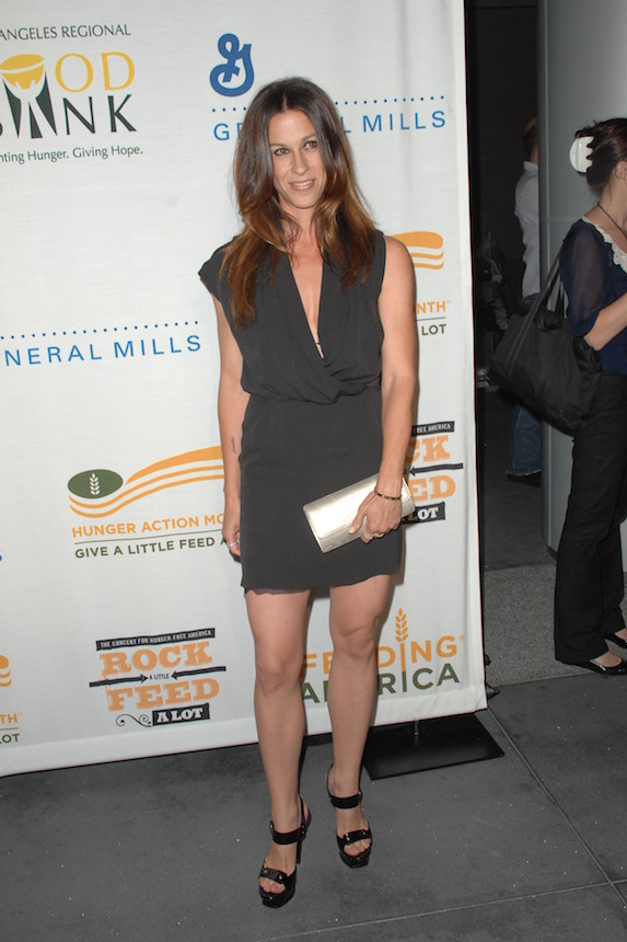 Alanis Morissette wears a grey mini dress and strappy pumps while attending a benefit concert in 2009