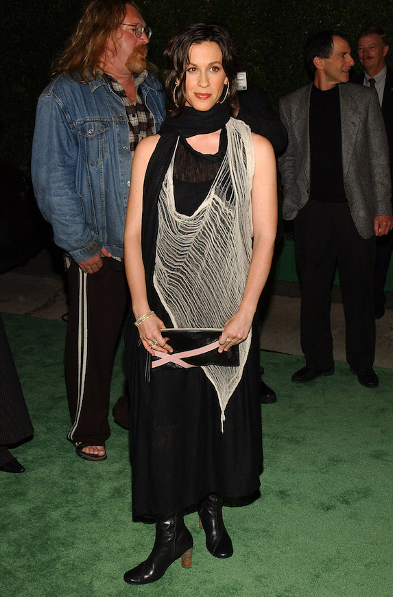 Alanis Morissette wears a black dress, beige overlay netted shawl and black boots to the Environmental Media Awards in 2003