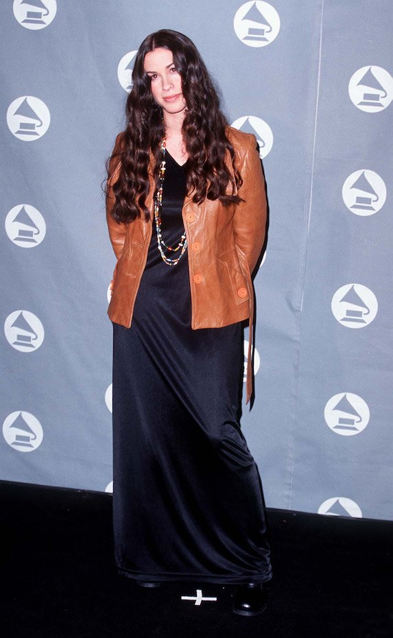 Alanis Morissette wears a black satin floor-length dress and leather jacket to the 1996 Grammy Awards