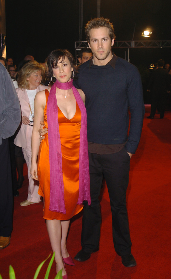 Alanis Morissette wears an orange satin dress and fuchsia neck scarf to the 2004 Juno Awards alongside then-fiancée Ryan Reynolds