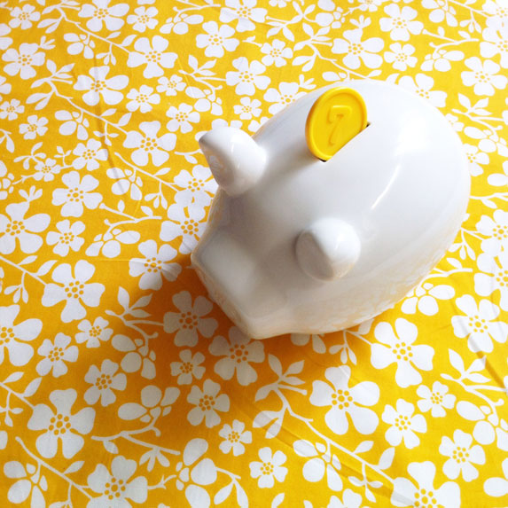 white piggbank on mustard floral tablecloth