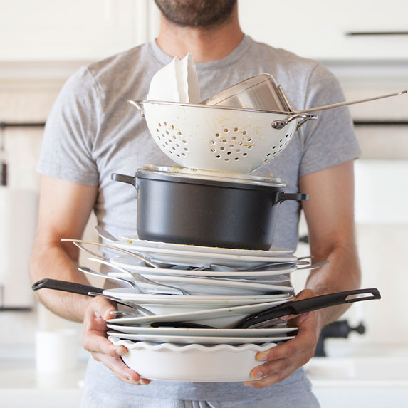 man holding pile of dishes