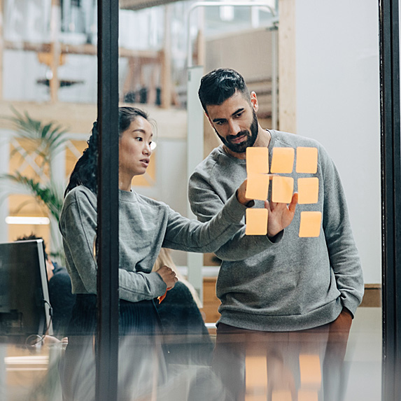 Woman asking man for help in front of board with Post-Its