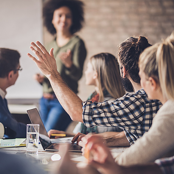 Woman running meeting while man has hand up to ask question
