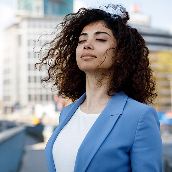 Woman taking a deep breath outside
