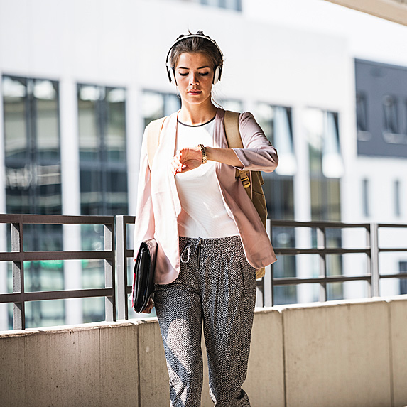 Woman looking at watch walking into work