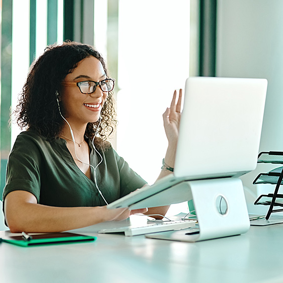 Woman sitting at tidy desk, working on laptop