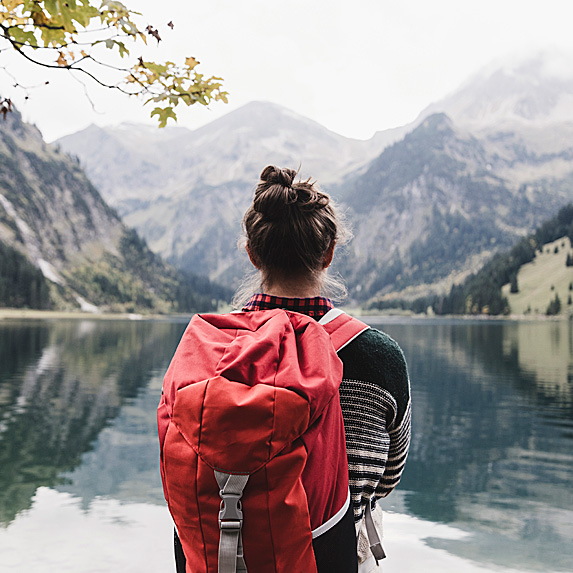 Woman with backpack, starting at mountains in Austria