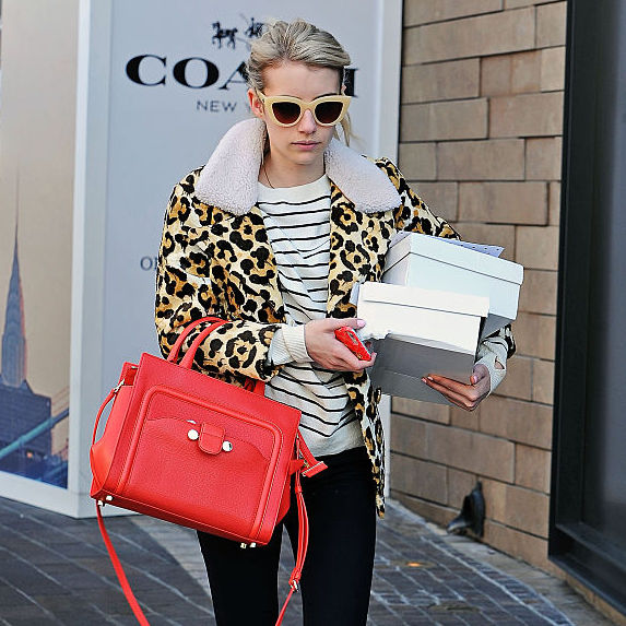 Emma Roberts wearing a leopard print jacket, striped shirt and holding a bright red handbag