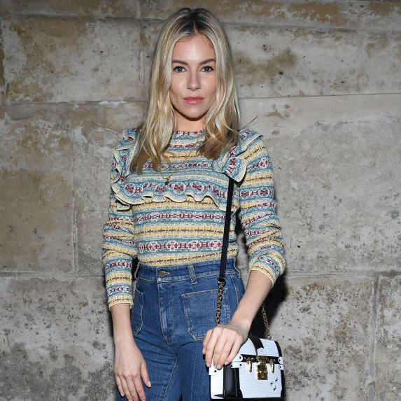 Sienna Miller wearing a frilled multicolour sweater and blue jeans