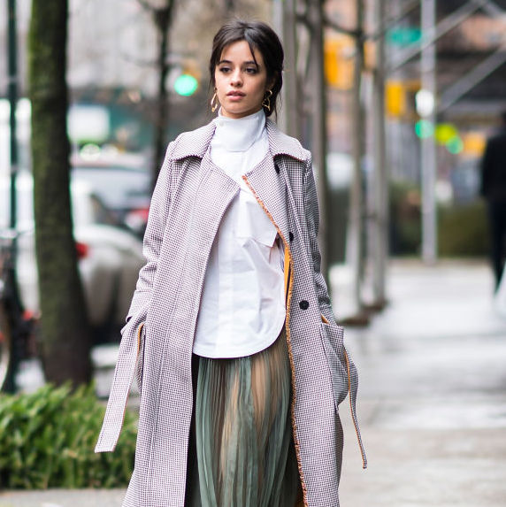 Camila Cabello wears a lavender coat, white button up shirt and sage-green tulle skirt