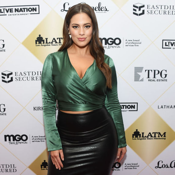 Ashley Graham wears a green satin wrap shirt and a leather skirt