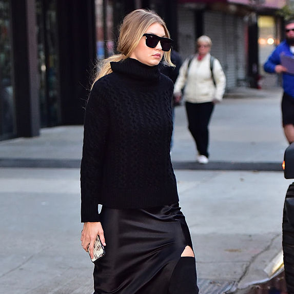 Gigi Hadid in black sunglasses, black turtleneck sweater, and black silk skirt