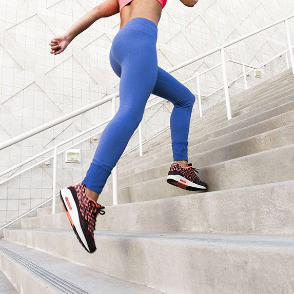 Woman running upstairs for a workout.