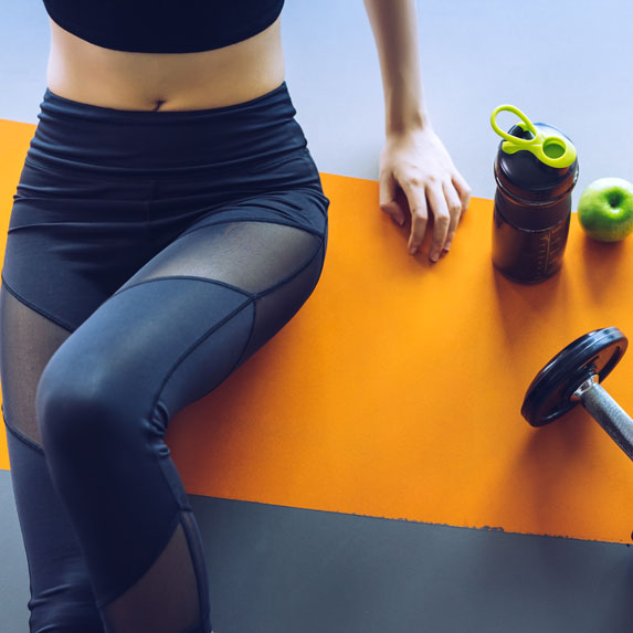 Woman in workout tights sitting on a yoga mat.