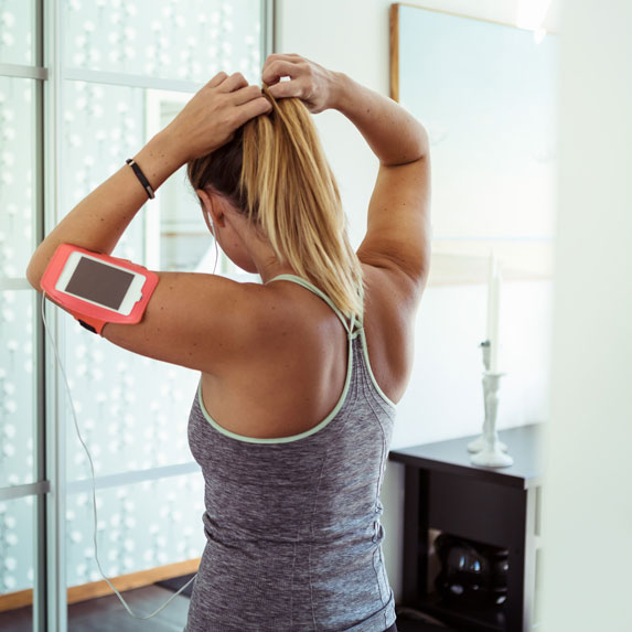 Woman tying a ponytail before working out.