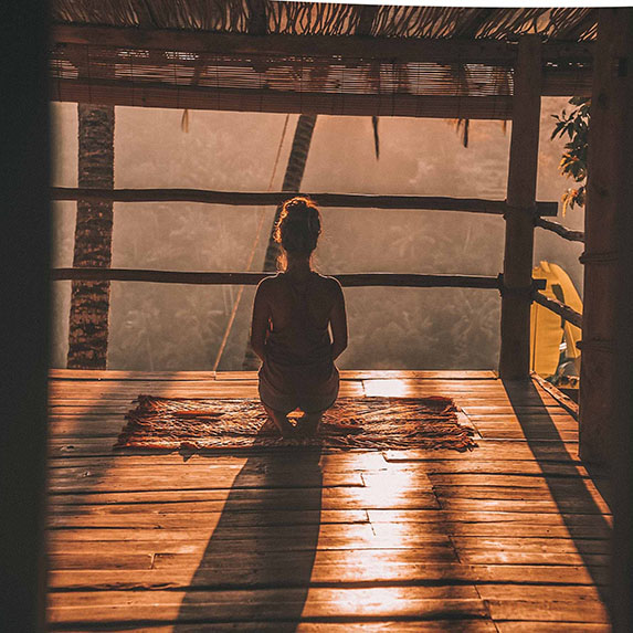 woman mediating in wooden hut