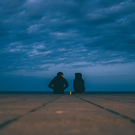 couple sitting on cement at night
