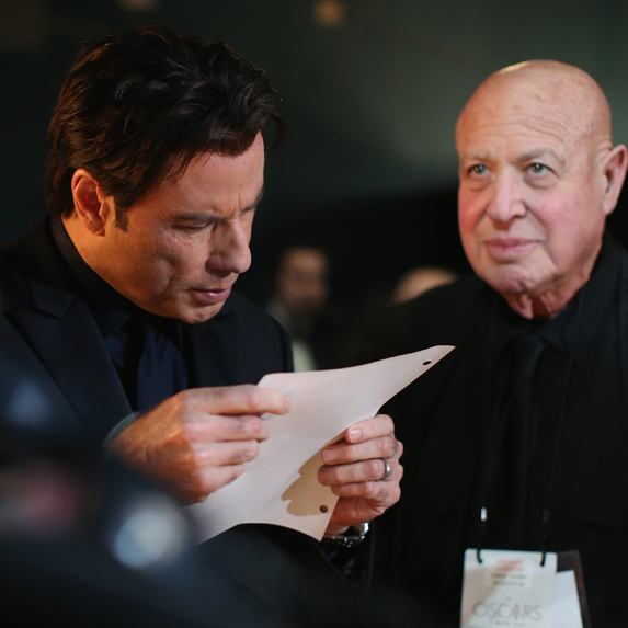 John Travolta looking at notes backstage during the Oscars