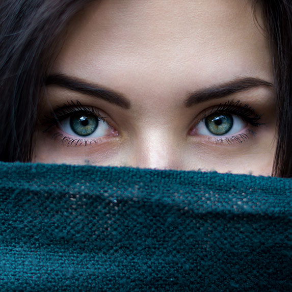 woman looking over scarf