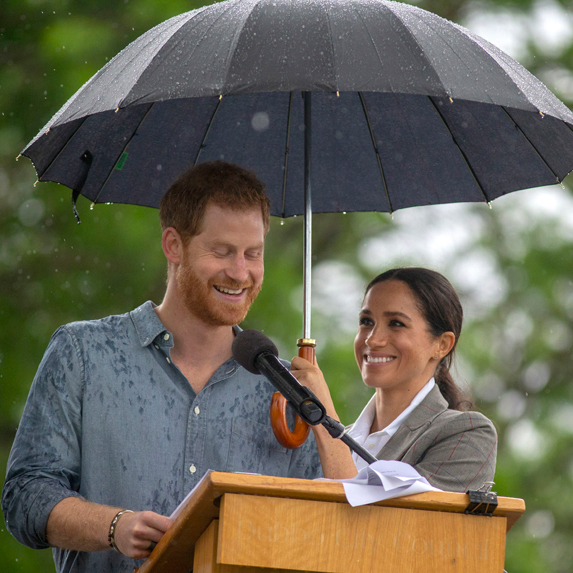 Prince Harry gives a speech in the rain while Meghan Markle holds an umbrella over his head