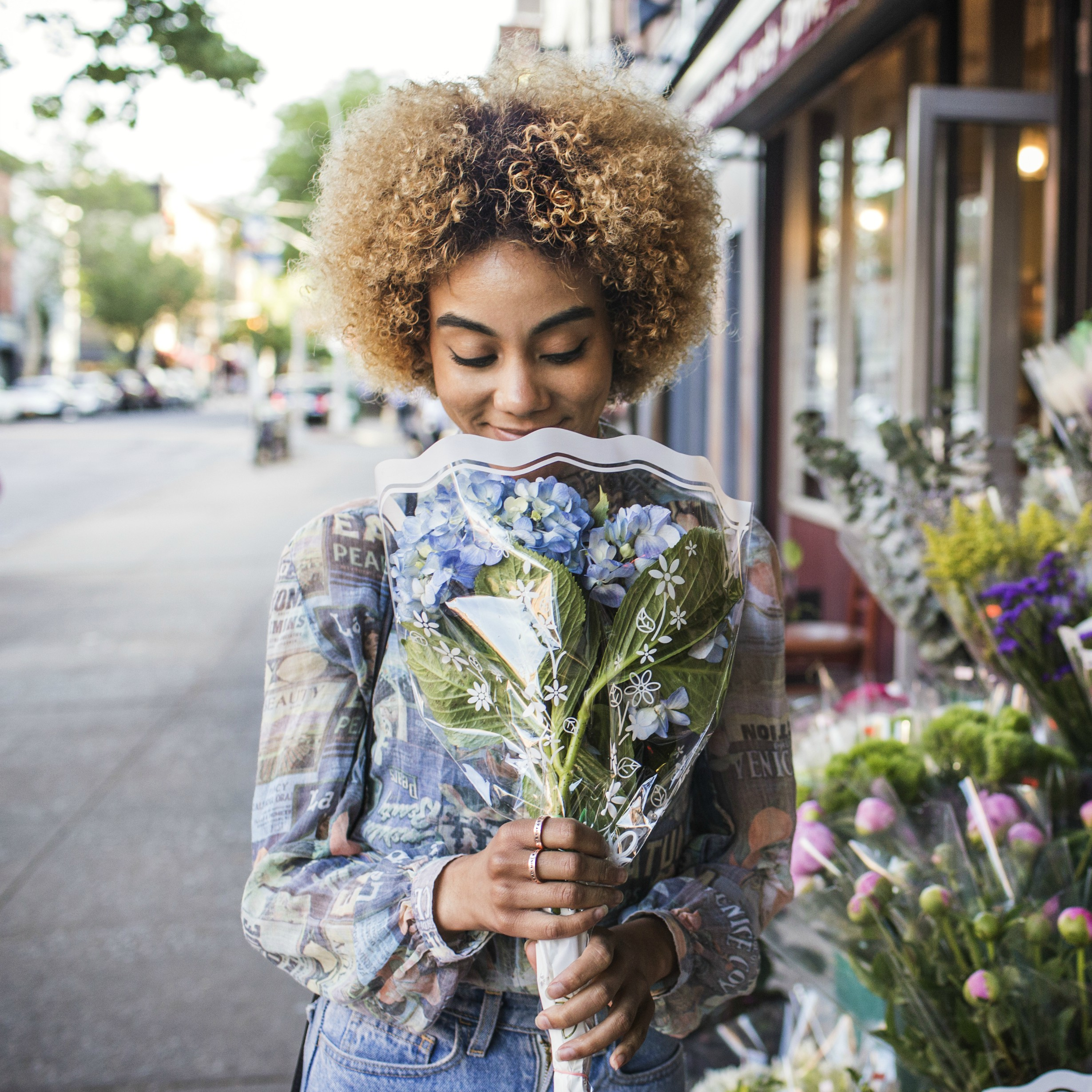 woman holding a bouquet of purple flowers and smelling