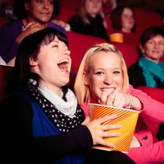 two women eating popcorn in movie theatre laughing