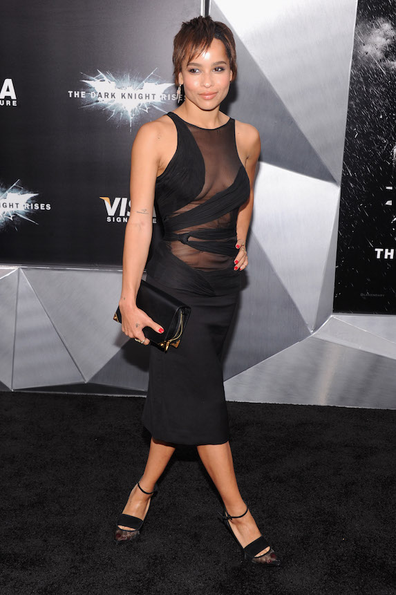 Zoe Kravitz wears a black fitted dress with sheer details and black pumps during a red-carpet appearance in 2012