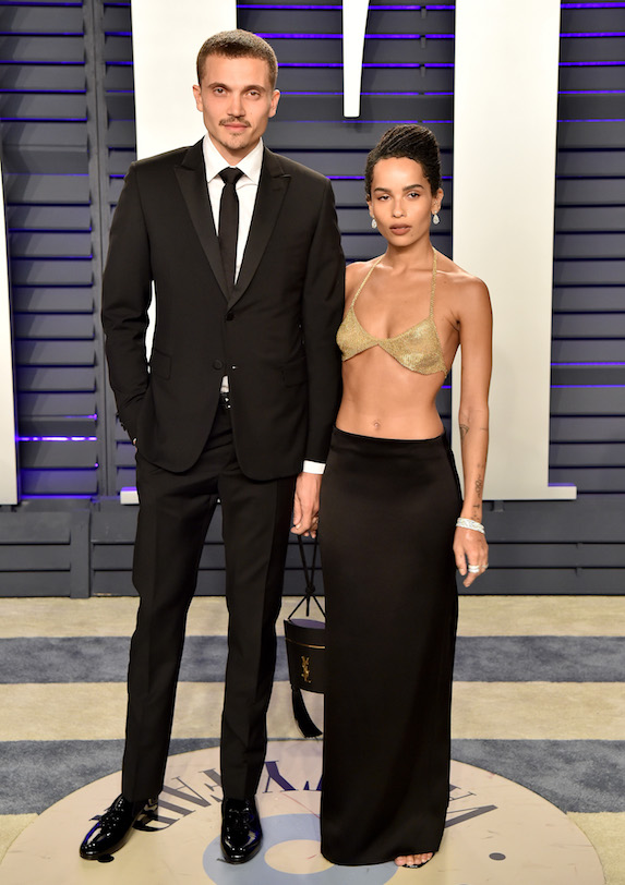 Zoe Kravitz wears a bikini-style top and maxi skirt while posing alongside husband Karl Gusman at the Vanity Fair Oscar Party in 2019