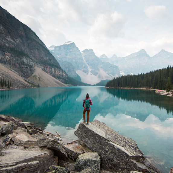 Person standing at a mountain lake