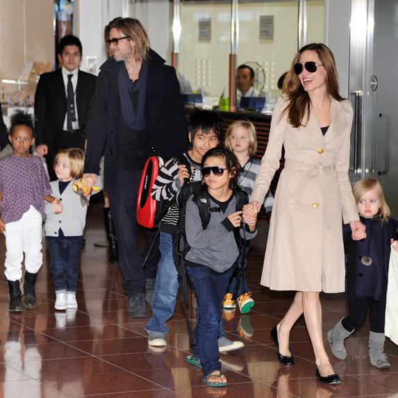 Brad Pitt and Angelina Jolie guide their six kids through an airport terminal
